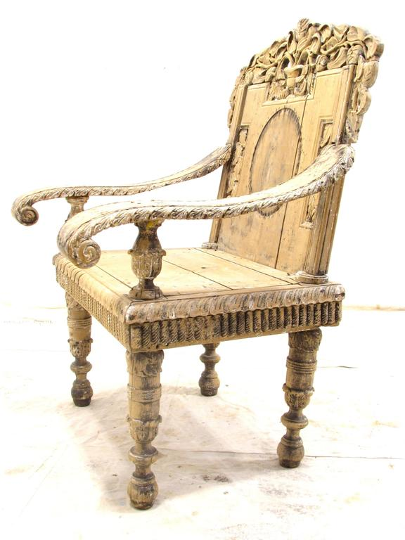 Very beautiful worn and weathered antique chair with elaborate arms and legs with detailed carvings.