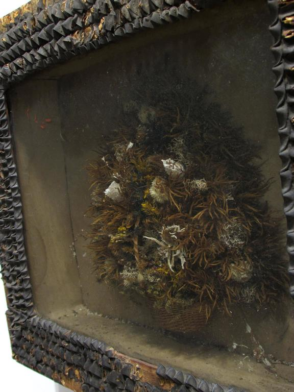 Beautiful very old antique dried flower arrangement in basket framed diorama with old seed pods on frame with old wallpaper on back this is a great piece of early Folk Art with old poured bubbled glass.