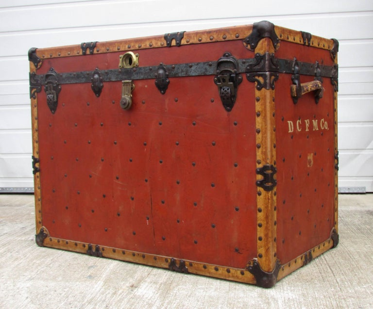 "Large shipping trunk from a circus made of riveted hard deep red fiber over wood with velum edging and metal details perfect height for sofa table made and labeled by ""J H McNamara Trunk Works Chicago"""