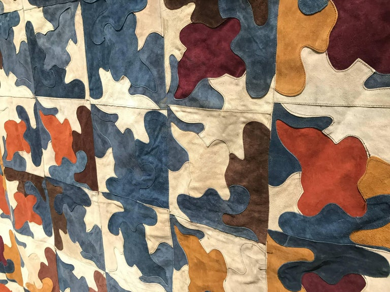Suede rug with multicolored shaped pieces sewn into an abstract design could be used as wall hanging or bedspread.