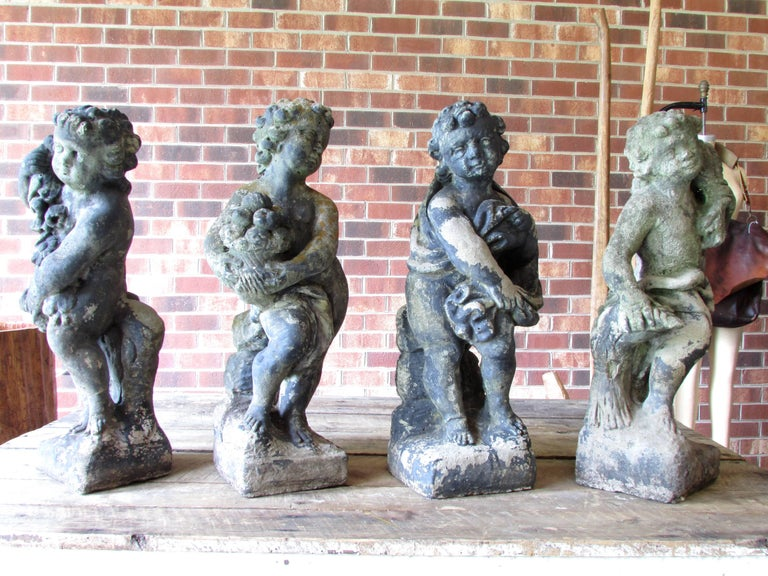 Set of four cast stone cherub statues depicting the four seasons based on Greek classical mythology the cherub with cloth and crossed arms to signify the cold temperature winter, cherub with fresh picked flowers depicting spring, cherub with basket