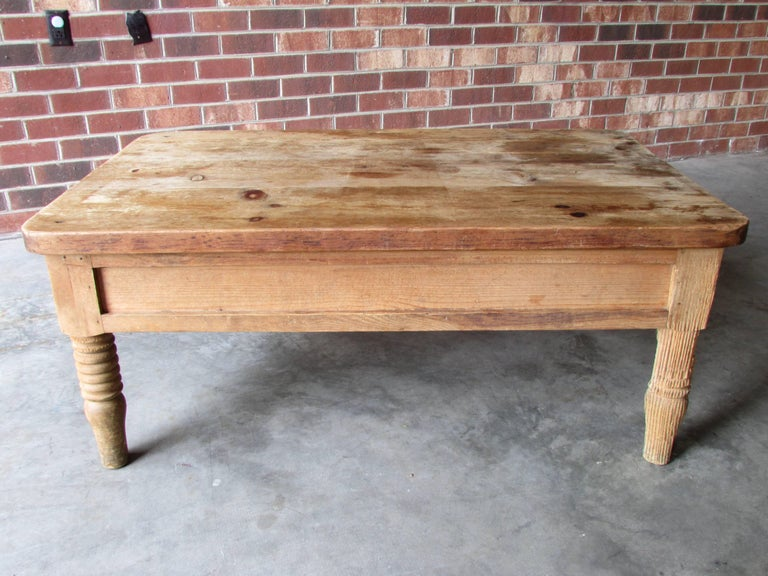 Rustic pine coffee table with a very worn and weathered finish has two drawers on either side with hand-forged iron pull handles.