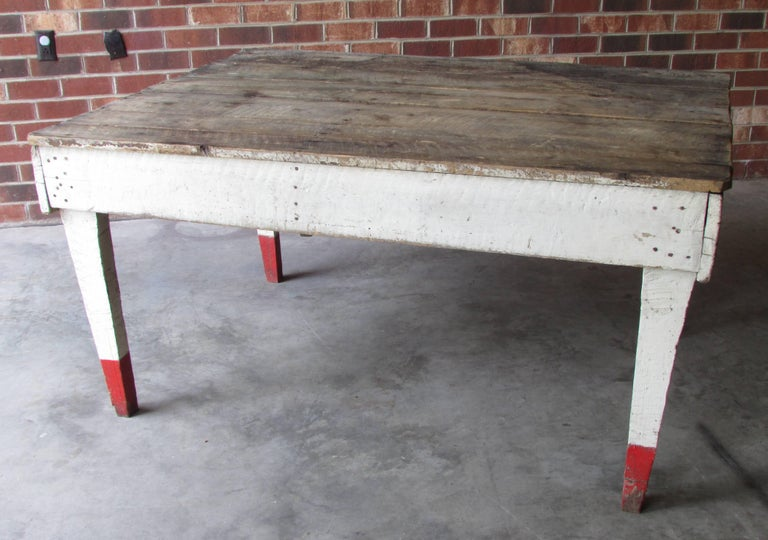 Rustic country farm table with rough sawn top and white painted sides and legs with red tips from Appalachian Mountains.