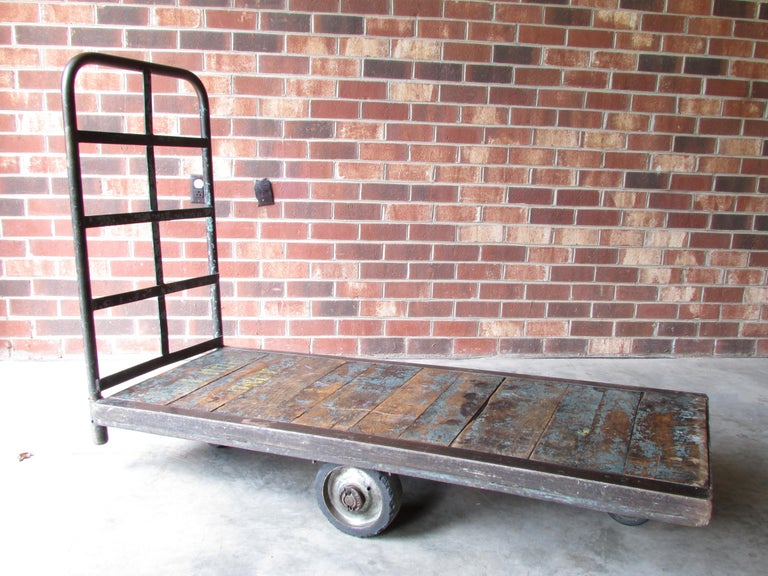 Worn and weathered antique rolling Industrial cart with metal frame and wooden slat deck has removable metal handle and brace and