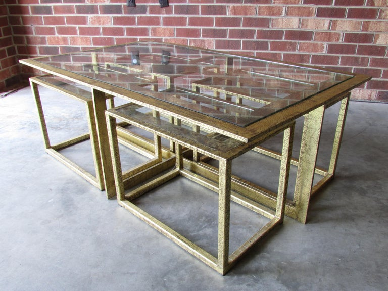 Beautiful coffee table with four smaller tables pushed underneath to bring out as needed metal frame is textured and has gold gilt finish and the inset glass is églomisé painted very much inspired by French 1940s furniture.