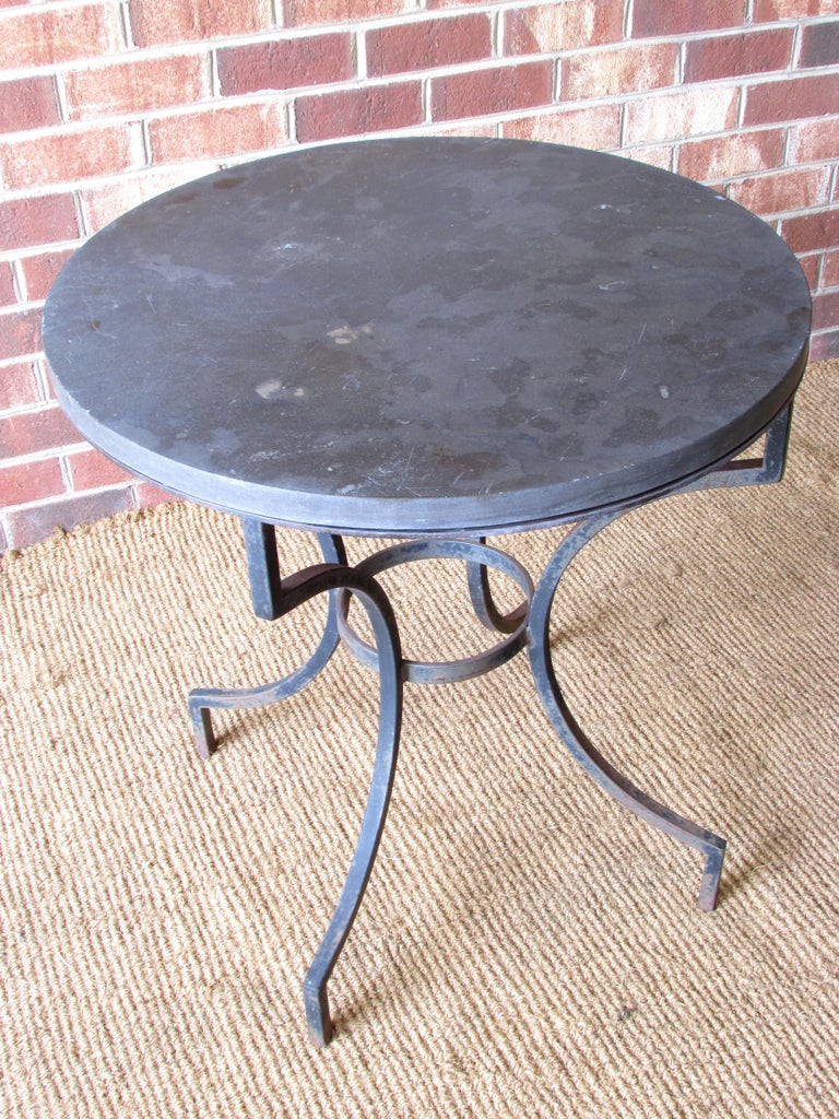 Lamp table with wrought iron base and round slate top.