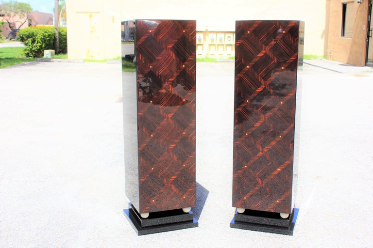 Beautiful pair of French Art Deco exotic Macassar ebony mother-of-pearl accents pedestals, circa 1940s. Square geometric bases with wood four balls ivory finish. These pedestals are Macassar ebony and black lacquer, with mother-of-pearl accents,