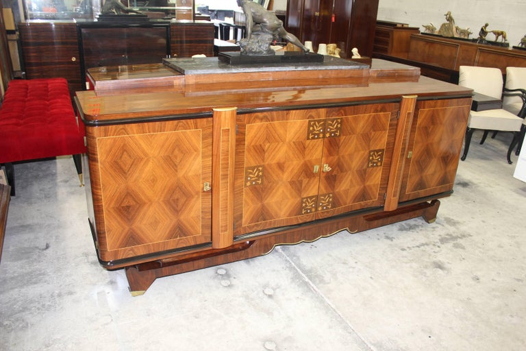 This stunning French Art Deco sideboards or buffet in the style of Jules Leleu is from the 1940s. Having beautiful mother-of-pearl inlay with gorgeous marquetry. Bronze detail, the craftsman ship is incredible, has marquetry along with floral and