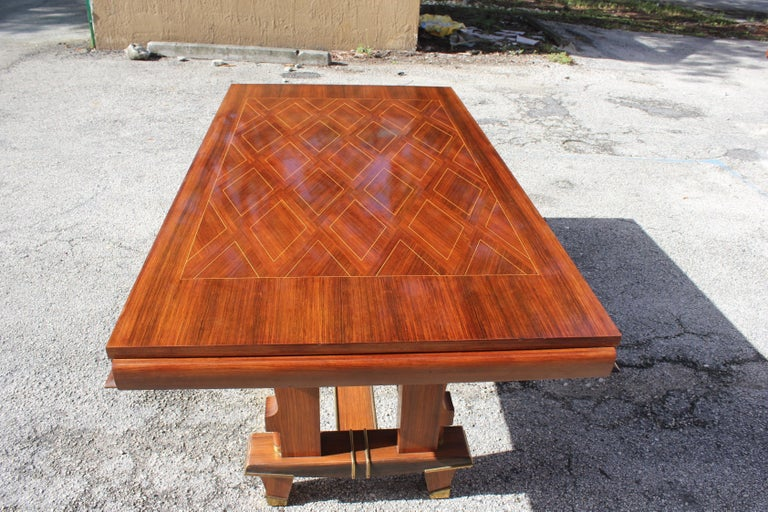 Beautiful French Art Deco dining table or desks and writing tables rosewood with diamond inlay marquetry by Jules Leleu style. The top of the table has geometric design. The base of the table have bronze hardware accents, please note these dining