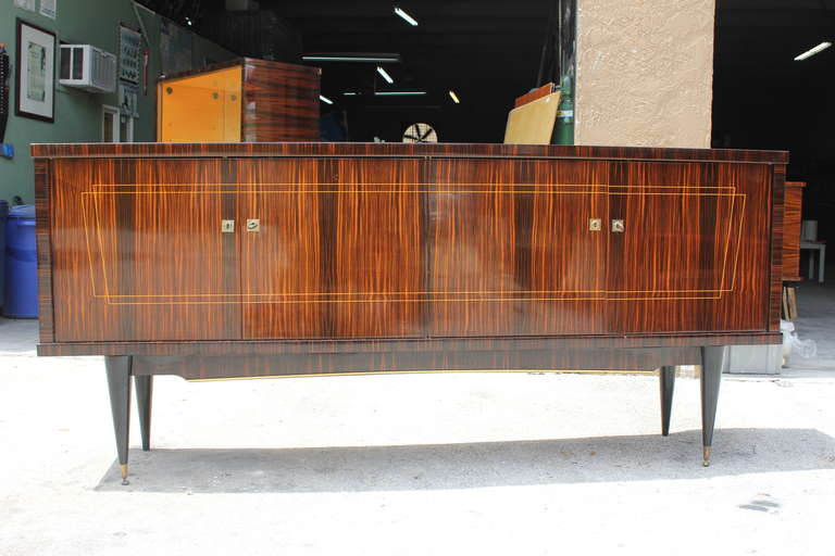 Long French Art Deco exotic Macassar ebony sideboard or buffet, circa 1940s. With one drawers inside, and bar section, two shelves wood shelves adjustable, and you can remove the shelves if you need more space, four legs with beautiful bronze