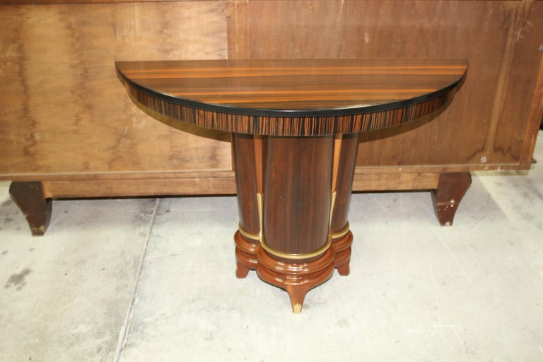 Classic French Art Deco exotic Macassar ebony console tables, circa 1940s. Beautiful Macassar ebony with demilune Macassar top and beautiful design centre base, lacquer finish in both side, beautiful bronze hardware detail, finish in both side,