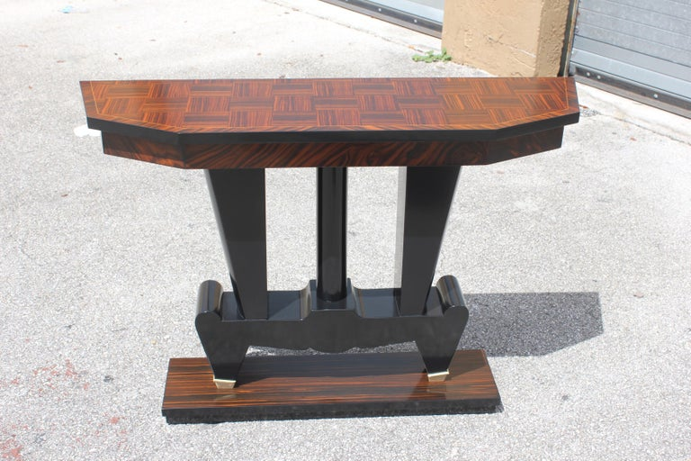 Unique French Art Deco exotic Macassar ebony console tables, circa 1940s. Beautiful Macassar ebony with black lacquer centre base, finish in both side, beautiful bronze hardware detail, that rest on makes it ideal for use as a bedside table or for