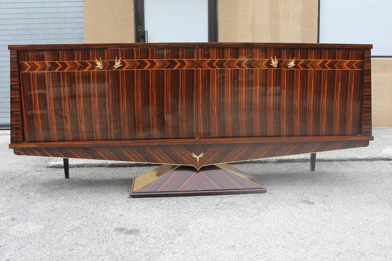 An absolutely fantastic designer French Art Deco exotic Macassar ebony sideboard, circa 1940s. Credenza is set on a center pedestal, truly one of a kind piece! Beautifully detailed throughout, interior finished in lemonwood. Excellent condition.