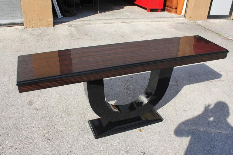 Spectacular French Art Deco exotic Macassar ebony console tables, circa 1940s. Beautiful Macassar ebony with black lacquer U base, High gloss lacquer finish in both side, French estate items.
