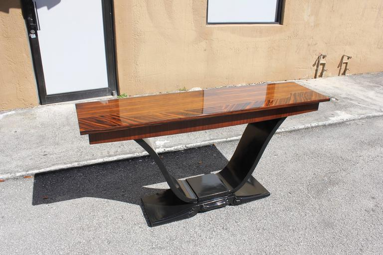 Spectacular long French Art Deco exotic Macassar ebony console tables, circa 1940s. Beautiful multi color Macassar ebony with black lacquer U-base, high gloss lacquer finish in both side, from France, Paris.