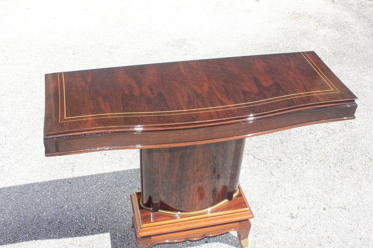 A stunning French Art Deco palisander console tables by Jules Leleu, circa 1930s. Beautiful inlay and bronze banding around base. Exquisitely crafts. Refinished with a high gloss finish. French estate pieces.
