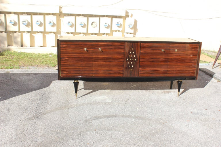 Beautiful French Art Deco Macassar ebony sideboard/buffet with diamond mother-of-pearl center, circa 1940s. Very nice sideboard with diamond Mother-of-Pearl Center with the Macassar ebony wood the sideboard are in very good condition, the piece have