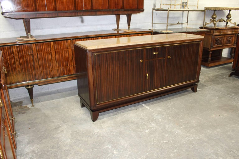 Beautiful French Art Deco Macassar ebony wood sideboard or buffet designed by Maurice Rinck. Mahogany wood interiors, with all adjustable shelf, with three doors one drawer, all with gilt bronze hardware with marble top. Original finish, circa 1940s.