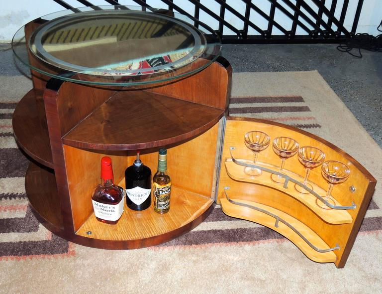 "A sleek round table with hidden bar cabinet was ""all the rage"" in the Art Deco Era. In this piece, a beautiful walnut cabinet has two compartments to hold bottles and glasses, nice shelving on the exterior for display and an etched round mirror as"