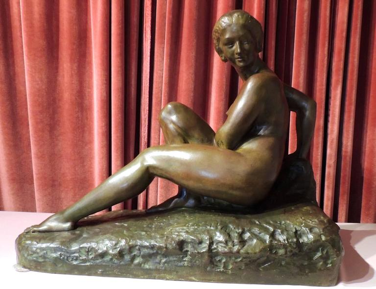 An Art Deco sculpture as substantial as it is beautiful, this work is a bronze statue by Marcel Bouraine. A seated nude in a demure pose, it has acquired a rich patina. The base is an integral part of the piece, also cast in bronze and bearing his