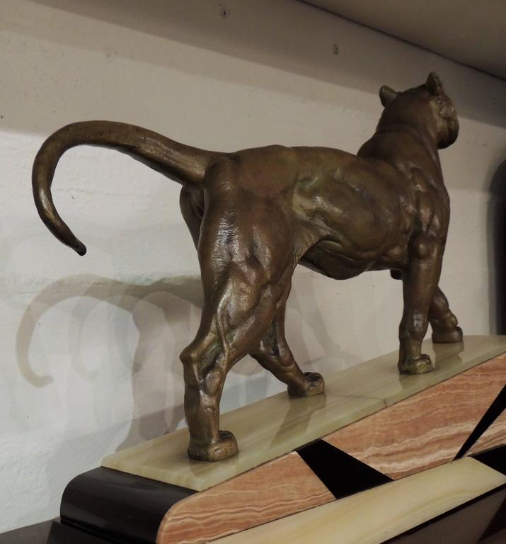 """An Art Deco era bronze statue of a lion with a great marble base of three tones inlaid in geometric shapes. The lion is powerfully rendered, its expression and musculature well defined.  Throughout history, the Lion has been known as the """"king of"""