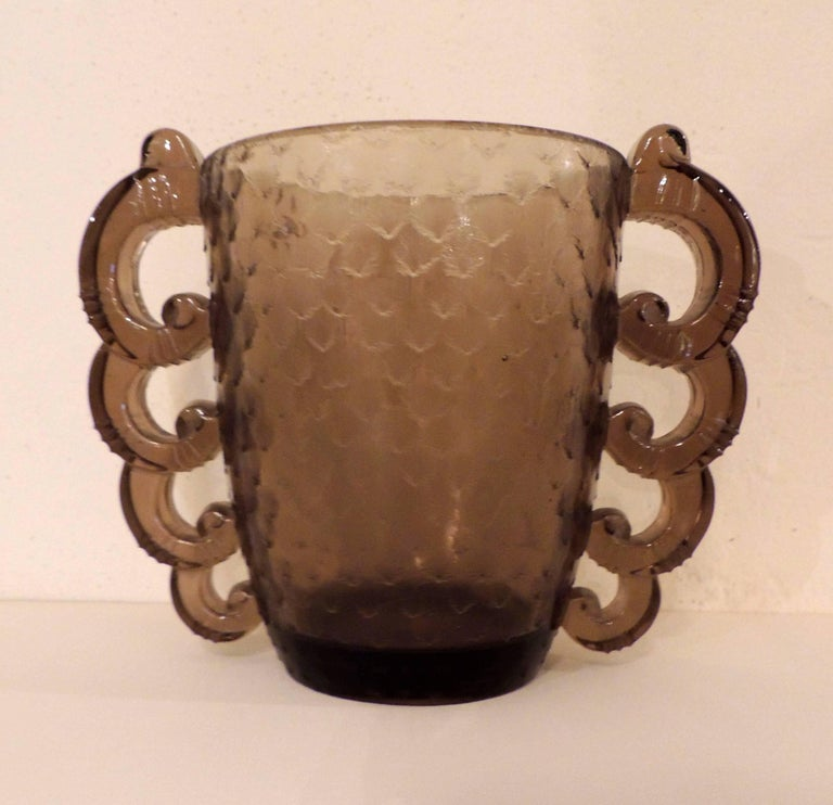 """A French Art Deco glass vase in a smoky """"topaz"""" tone with a great textured surface and those dramatic scalloped """"handles"""" that echo some of the shapes created by the glass masters such as Lalique. This example was made for Daum by Pierre D'Avesn."""