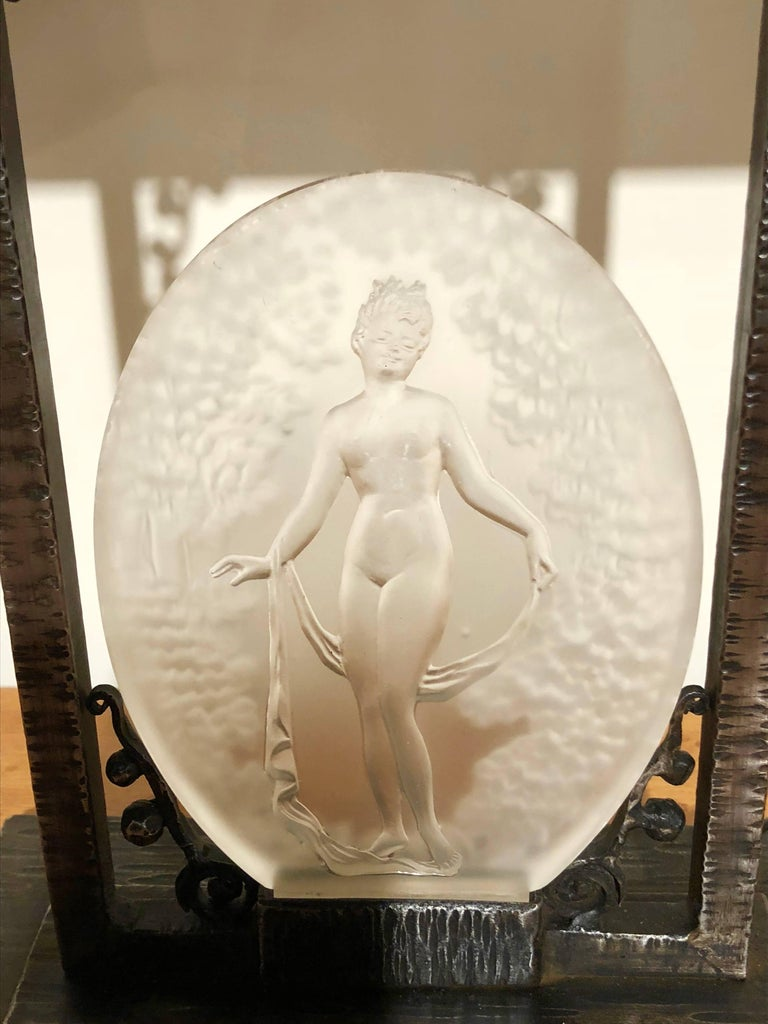 """French Art Deco table lamp created by Pierre D'Avesn, circa 1930. Unique combination of French iron """"fer forge"""" with a combination of a horizontally banded frosted shade and a glass acid etched medallion depicting the female form surrounded by a"""