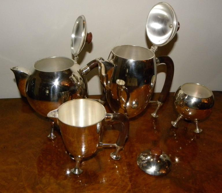 """His wild, whimsical and somewhat """"space age"""" silver tea and coffee set is one of the most unusual we have ever had. Curved wooden handles and pieces that rest on silver feet, it takes the formal and traditional coffee-tea-cream-and-sugar combination"""