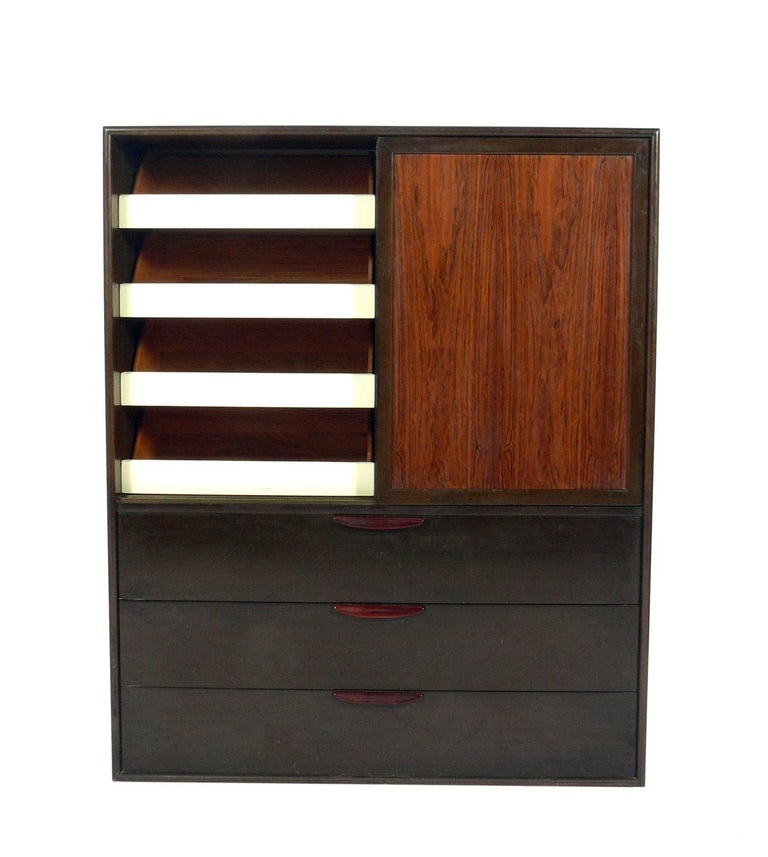 Tall rosewood chest of drawers or Dresser, designed by Harvey Probber, American, circa 1960s. It offers a voluminous amount of storage. It features sliding doors at the top that open to reveal four deep drawers on the left, and three deep sliding