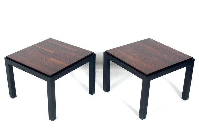 Pair of rosewood and black lacquer end tables, designed by Milo Baughman for Thayer Coggin, American, circa 1960s. They are a versatile size and can be used as side or end tables in a living area, or as nightstands in a bedroom.