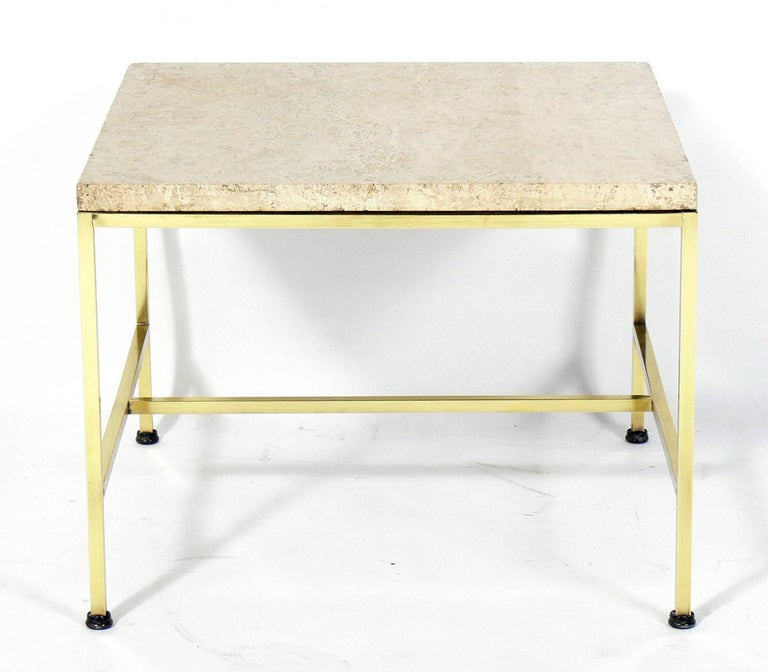 Brass and travertine side table, designed by Paul McCobb, American, circa 1950s. It is a versatile size and can be used as a side or end table, or as a nightstand. Brass frame has been polished and lacquered.