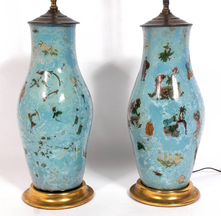 Pair of Robin's Egg Blue Asian Influenced Lamps, probably American, circa 1950s. They are constructed of reverse painted glass with Asian decorations on the interior of the glass and brass fittings. They have been rewired and are ready to use. The