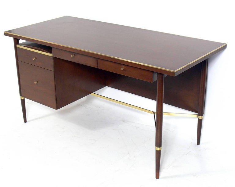 Clean lined modern desk, designed by Paul McCobb, American, circa 1960s. This desk is currently being refinished and can be completed in your choice of finish color. The price noted includes refinishing in your choice of finish color.