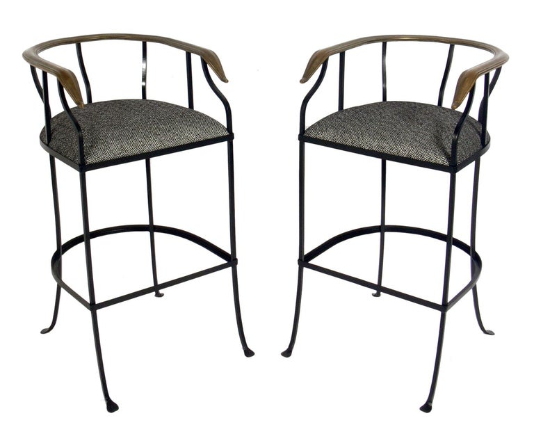 Pair of elegant brass and iron bar stools, American, circa 1950s. They have been beautifully restored with the iron frames painted and new black and white herringbone upholstery installed. The brass horseshoe backrests retain their warm original