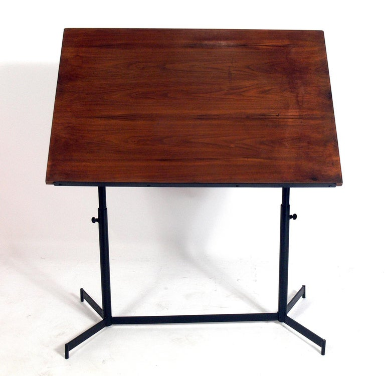 Midcentury drafting table or desk, American, circa 1950s. It is a versatile size and can be used as a drafting table, desk, easel, or dining table. Retains distressed original patina to the walnut top. Metal base has been repainted at some point.
