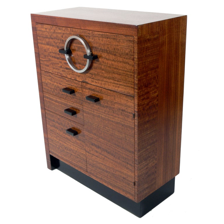 Modernist cabinet, designed by Gilbert Rohde for Herman Miller, circa 1930s. Constructed of exotic East Indian laurel wood with black lacquered trim and nickel plated metal hardware. This is a versatile pieces and can be used as a desk, cabinet,