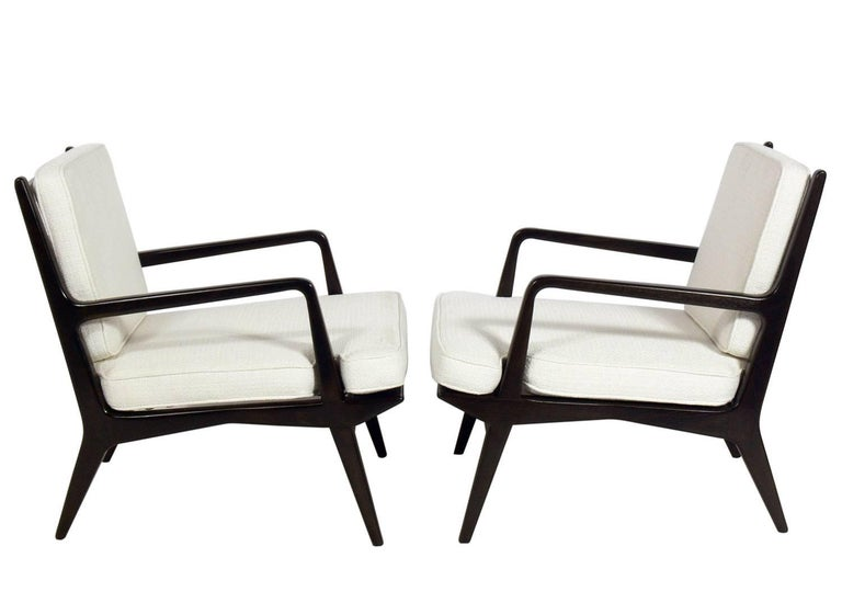 Pair of lounge chairs, designed by Carlo di Carli for Singer and Sons, American, circa 1950s. These chairs have been completely restored in an ultra deep brown lacquer and an ivory color woven upholstery.