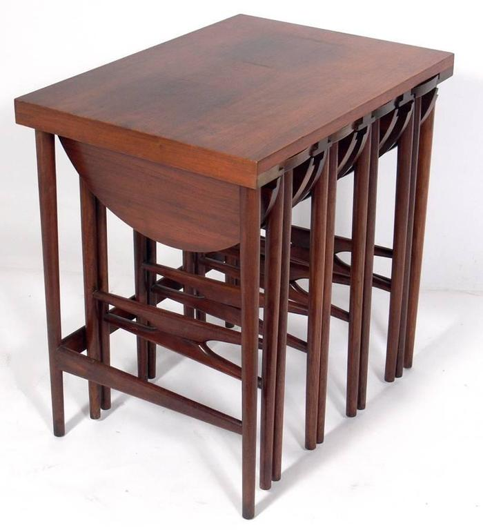 Ingenious Set of Modernist Nesting Tables, designed by Bertha Schaefer for Singer and Sons, circa 1950's. Beautiful graining to the Italian walnut, especially to the table tops This set is great for entertaining, as the large rectangular table can