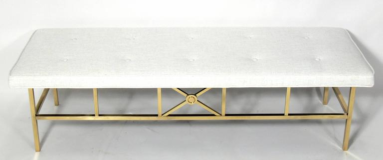 Elegant modern brass bench, in the manner of Paul McCobb, American, circa 1960s. The brass base has been polished and lacquered and it has been reupholstered in an ivory color herringbone fabric.