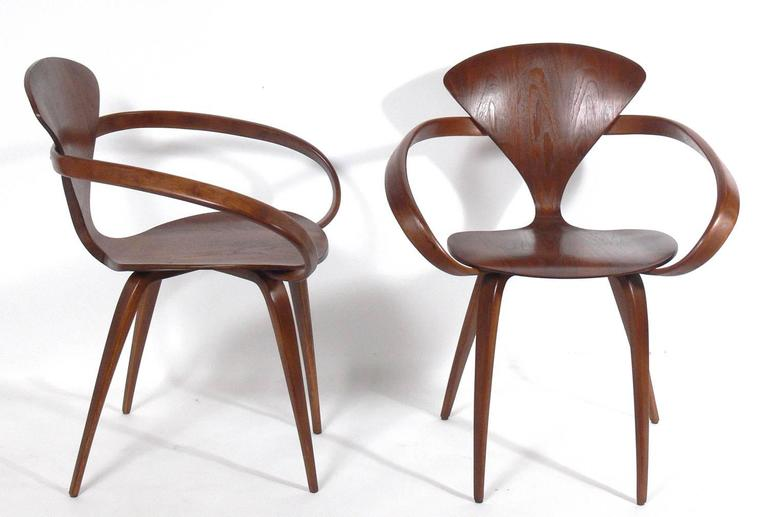 Set of 12 sculptural dining chairs, designed by Norman Cherner for Plycraft, circa 1950s. They have all been refinished and look great. The price noted below is for the set of 12 dining chairs, two armchairs and ten side chairs.
