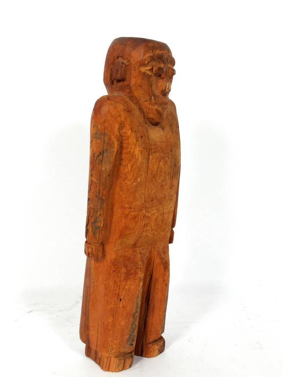 Hand-carved folk art man sculpture, American, believed to be circa 1940s. Playful shrugging form. Retains warm original patina.