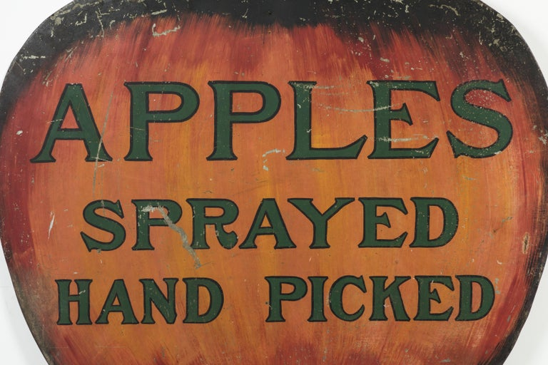 Vintage heavy sheet iron trade sign with fantastic subject matter. Giant apple with original paint surface and excellent hand lettering. Very dynamic piece of American Folk Art. Heavy iron hooks on bottom.