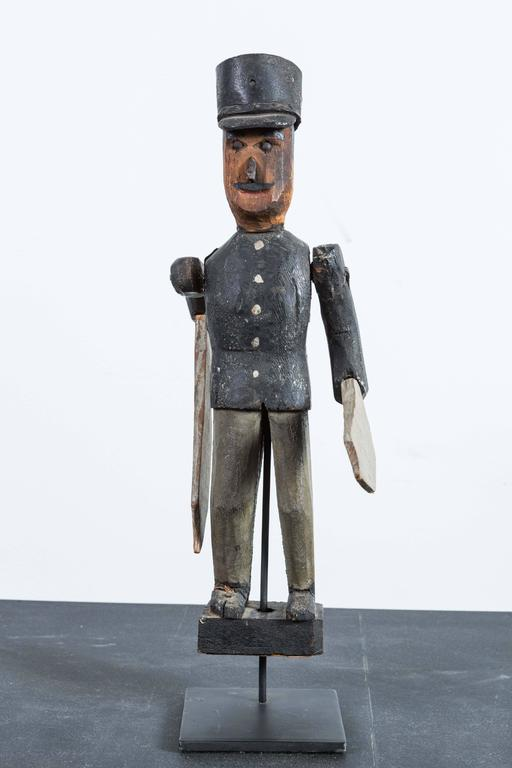 Carved and painted wooden soldier whirligig. Early 20th century American. Soldier has a leather hat with wooden brim. Presented on simple custom museum stand.