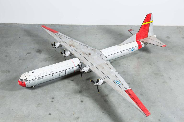 "Mid-century large-scale wood carved Folk Art Cargomaster C-133A. An actual barn find discovered in Washington State farm country. Hand-carved and painted. Two pieces: wing piece attaches and bolts to fuselage. Hand-painted markings read ""Douglass"