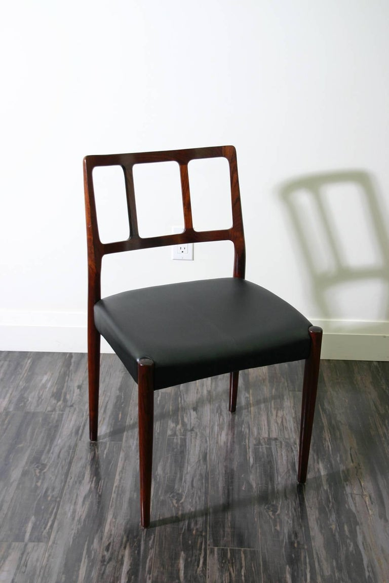 A set of four Danish 1960s rosewood designed by Johannes Andersen. Manufactured by Uldum Møbelfabrik with black leather seats.