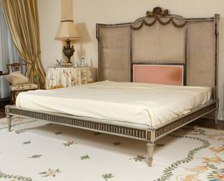 Louis XVI style painted and carved wood king-size bed. The backboard finished with cane-work.  Dimensions: from floor to railing 9.5 inches                      from floor  to base of mattress 14 inches