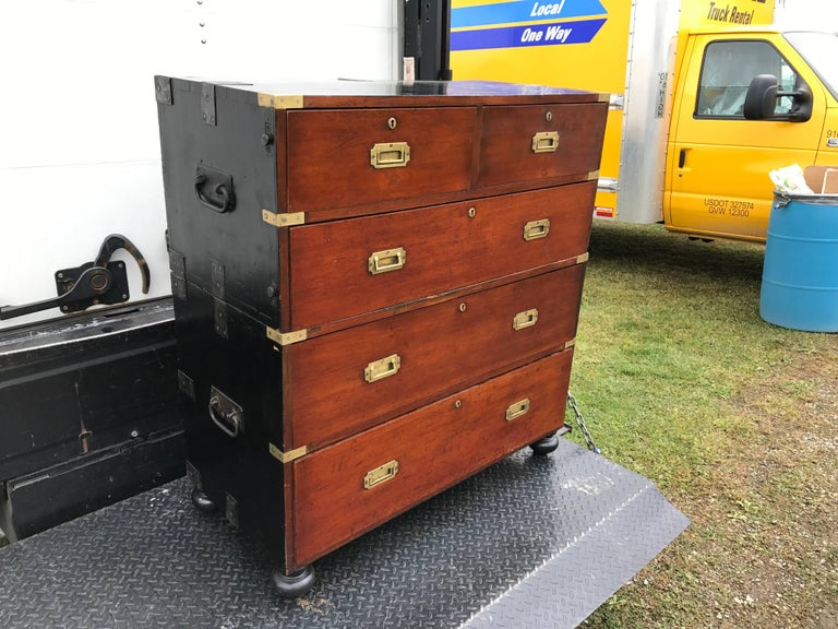 Great vintage mahogany and painted wood two-part campaign chest, the front fitted with typical flush mounted brass hardware, the top and sides fitted with unusual steel reinforcement and fittings for traveling use.