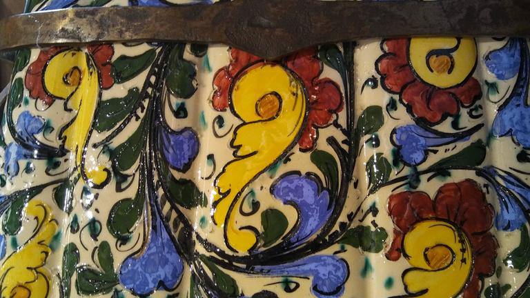 Arts and Crafts period Italian Majolica pottery fan shaped umbrella stand  on its custom wrought iron two handled base. The floral elements are tube lined to enhance the vivid coloration; the vertical bands of the lower are separated from the