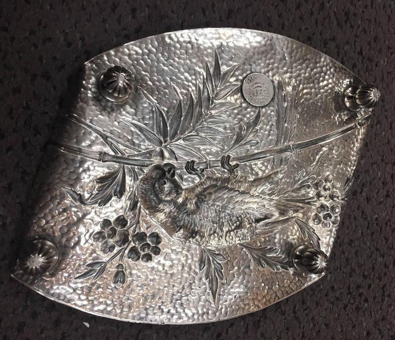Aesthetic Movement hammered silver plate footed card tray with softly folded ends by Boston silversmith, James W Tufts (1835-1902). The tray depicts a charming vignette of a macau or parrot perched on a bamboo branch amid a floral surround. Makers