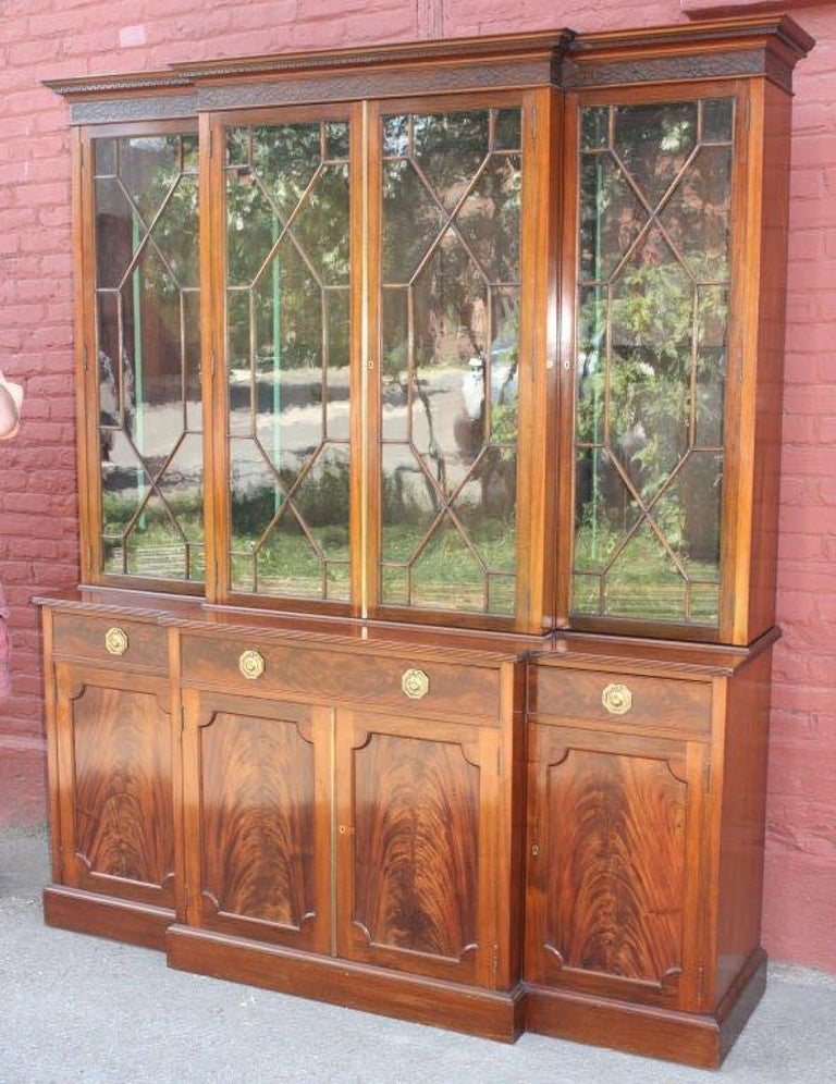 George III style mahogany breakfront three bay bookcase cabinet, the ogee dentillated over blind fretwork cornice with four astragal glazed doors over one long and two short drawers atop four matched flame mahogany doors. Brass tag inside door,